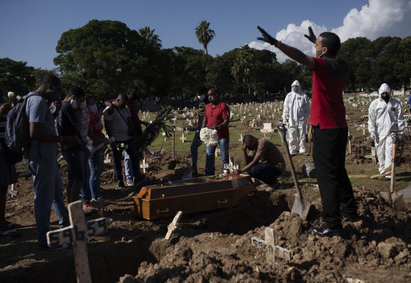 Relatives pray during the burial of Amanda da Silva, who died of COVID-19 at the Caju Cemetery, in Rio de Janeiro, Brazil, Wednesday, May 20, 2020. (AP Photo/Silvia Izquierdo)