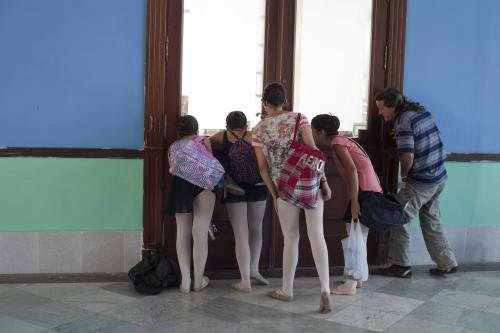"In this April 3, 2013 photo, ballet students and a student's father watch a class through a window at the National School of Ballet in Havana, Cuba. The school was founded seven decades ago by famed prima ballerina assoluta Alicia Alonso, now age 92, who is probably the most recognized person in Cuba not named ""Castro."" (AP Photo/Ramon Espinosa)"