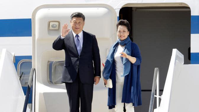 Presiden China Xi Jinping dan istrinya, Peng Liyuan melambaikan tangan setibanya di Hamburg, Jerman, Kamis (6/7). Sejumlah kepala negara telah tiba di Hamburg jelang pembukaan KTT G20 pada 7-8 Juli 2017. (AP/Michael Sohn)