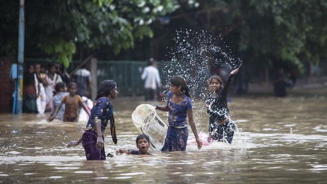 Anak-anak bermain di jalan yang tergenang air setelah hujan monsun di Gurgaon di pinggiran New Delhi (19/8/2020). Jumlah korban dari banjir tahunan di seluruh Asia Selatan naik menjadi hampir 1.300. (AFP/Xavier Galiana)