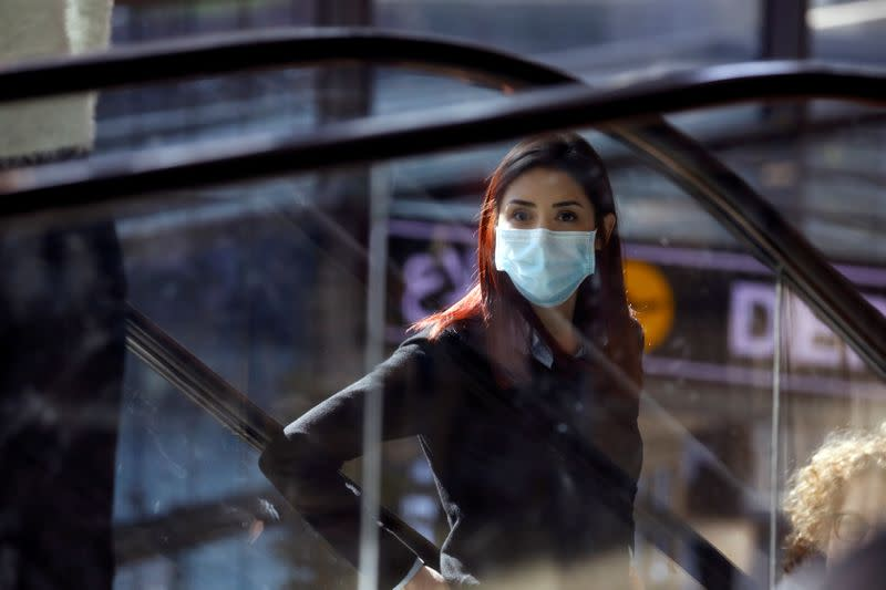 FILE PHOTO: A woman wearing a mask looks on at a terminal at Ben Gurion International airport in Lod, near Tel Aviv, Israel