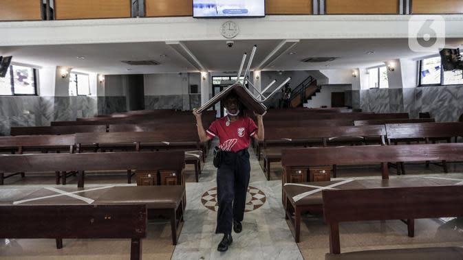 Karyawan memindahkan bangku untuk menyambut kenormalan baru di Gereja Protestan Indonesia Bagian Barat (GPIB) Effatha, Jakarta, Sabtu (4/7/2020). GPIB Effatha menerapkan protokol kesehatan seiring kembali dibukanya gereja tersebut untuk ibadah di tengah pandemi COVID-19. (Liputan6.com/Johan Tallo)