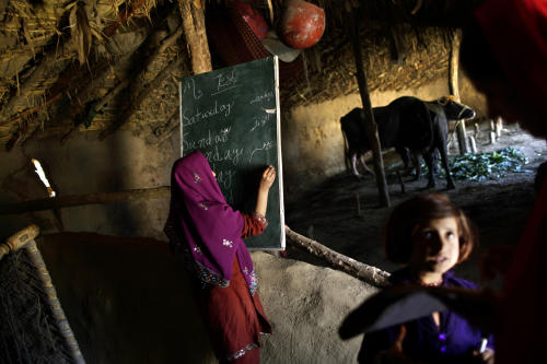 In this Wednesday, March 27, 2013, photo, a Pakistani schoolgirl, center, writes on the blackboard, while her teacher Warda Arshad, 20, right, check the homework of another student during their daily classes in a makeshift school set in a clay house, part of it is used as a cowshed, in a poor neighborhood on the outskirts of Islamabad, Pakistan. Wonder Woman and Supergirl now have a Pakistani counterpart in the pantheon of female superheroes _ one who shows a lot less skin. Meet Burka Avenger: a mild-mannered teacher with secret martial arts skills who uses a flowing black burka to hide her identity as she fights local thugs seeking to shut down the girls' school where she works. Sadly, it's a battle Pakistanis are all too familiar with in the real world.(AP Photo/Muhammed Muheisen)