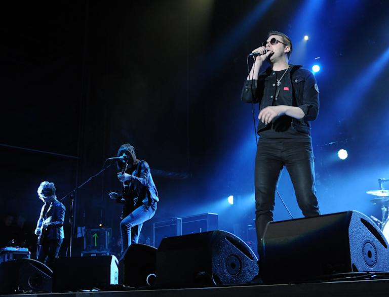 Kasabian lead singer Tom Meighan (R) and guitarists Jay Mehier and Sergio Pizzorno (L-R background), perform at Dubai Sevens stadium, Friday, February 10, 2012. The British band belted out such classics as Shoot The Runner and Club Foot to what seemed to be a predominantly British audience. Photograph: Peter Harrison/Yahoo! Maktoob