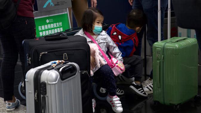 Seorang anak mengenakan masker duduk di antara koper-koper di Bandara Internasional Hong Kong di Hong Kong, Selasa (21/1/2020). Masker terjual habis dan pemeriksaan suhu di bandara dan stasiun kereta api menjadi norma baru di China menyusul merebaknya wabah virus corona. (AP/Ng Han Guan)