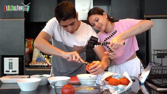 Belakangan, pasangan muda ini semakin tidak malu memamerkan kemesraan mereka dalam momen apapun. Seperti di foto ini, keduanya terlihat sedang syuting masak memasak untuk channel Youtub Al, El dan Dul. (Instagram/alghazali)
