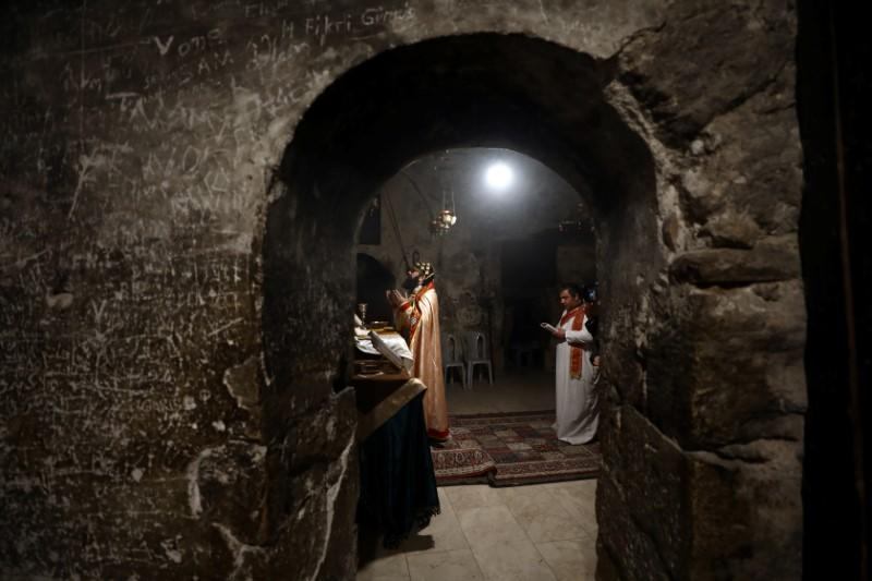 Worshippers pray inside the Syrian Orthodox section of the Church of the Holy Sepulchre, revered as the site of Jesus's crucifixion and burial, in Jerusalem's Old City