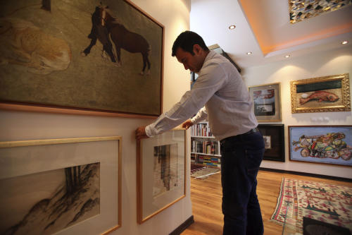 In this Thursday, July 11, 2013 photo, Iranian art collector Ali Bakhtiari places a painting of late Iranian painter Sohrab Sepehri, on the wall, at his house, in Tehran, Iran. (AP Photo/Vahid Salemi)