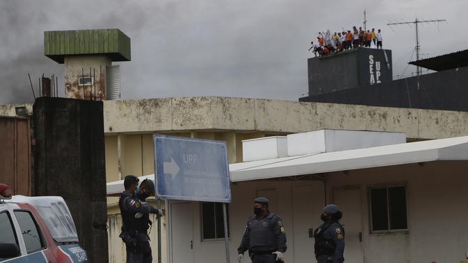 Polisi militer melakukan pengamanan saat narapidana melakukan protes dengan menaiki menara air di Penjara Puraquequara, Manaus, Brasil, Sabtu (2/5/2020). Mereka memprotes kondisi buruk dan pemberlakuan pembatasan kunjungan keluarga untuk mencegah penyebaran corona COVID-19. (AP Photo/Edmar Barros)