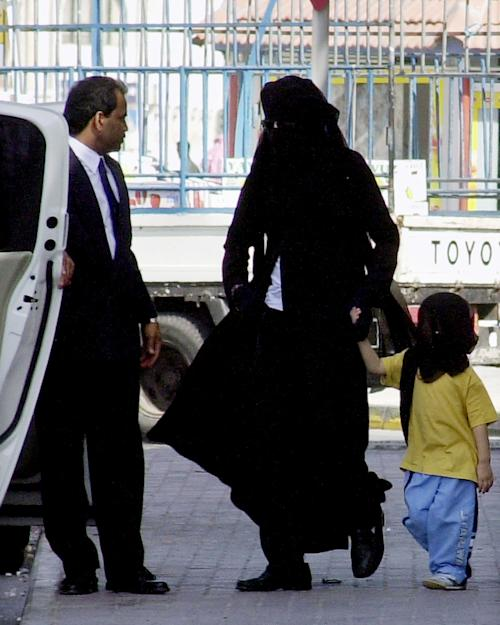 FILE - In this Jan. 25, 2006 file photo, Michael Jackson, center, wears an abaya, the traditional Arabic women's veil and all-covering gown, and holds the hand of one of his children, also veiled, as they walk toward their car behind a shopping mall, in Manama, Bahrain. Jackson, a reclusive resident of the Gulf island country since being cleared of child molestation charges, was accompanied by his sister, Janet, unseen, and two other children on the shopping outing. Jurors hearing a civil case in Los Angeles filed by Jackson's mother, Katherine Jackson, have heard numerous stories about the entertainer's devotion to his children as expressed through extravagant birthday parties and secret family outings. The tender moments have been described throughout the trial, which concluded its eighth week on Friday, June 21, 2013. (AP Photo/Hasan Jamali, File)