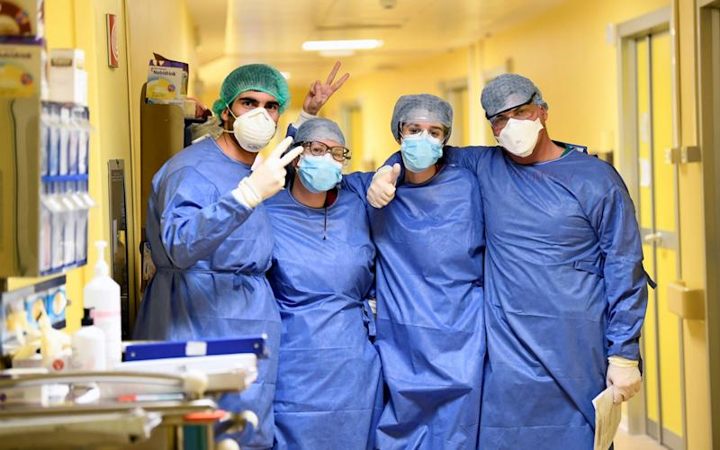 Medical staff in protective suits pose for a photo in the COVID-19 intensive care unit at the San Raffaele hospital in Milan - Reuters