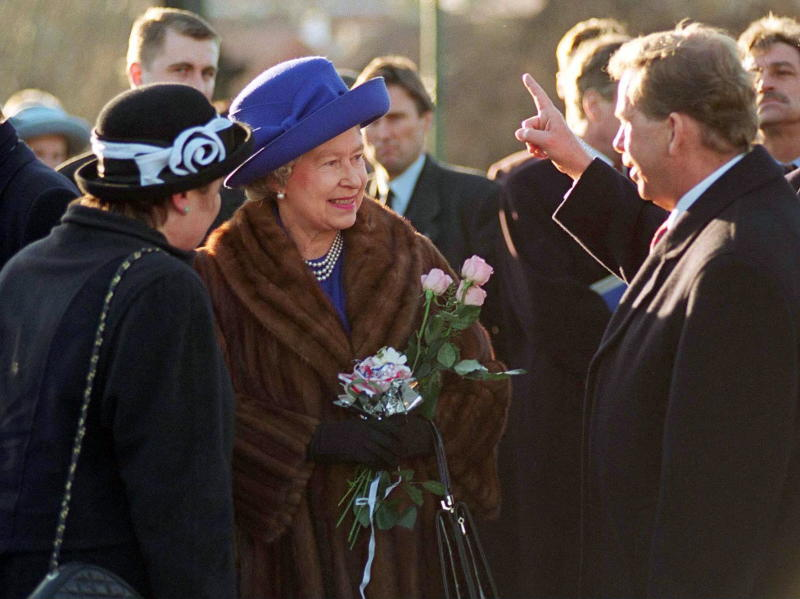 A photo of Queen Elizabeth wearing a brown fur coat and a purple hat in Prague in 1996.