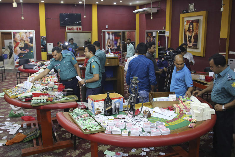In this Sept. 22, 2019, photo, police officers inspect seized gambling equipment at Victoria Sporting Club in Dhaka, Bangladesh. Security officials in Bangladesh are on the hunt for cash, gold and illicit weapons in a crackdown Prime Minister Sheikh Hasina ordered on illegal casinos, rooting out corruption among political elites that critics say has been allowed to flourish in a troubled democracy with no effective opposition. (AP Photo/Mahmud Hossain Opu)