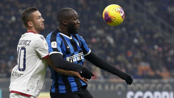 Striker Inter Milan, Romelu Lukaku, duel udara dengan pemain Cagliari, Sebastian Walukiewicz, pada laga Coppa Italia di Stadion Giuseppe Meazza, Rabu (15/1/2020). Inter Milan menang 4-1 atas Cagliari. (AP/Antonio Calanni)