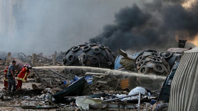Petugas memadamkan api setelah ledakan besar di Beirut, Lebanon, Selasa, (4/8/2020). Dua ledakan besar mengguncang ibukota Lebanon, Beirut, melukai puluhan orang, menghancurkan gedung-gedung dan mengirimkan asap besar mengepul ke langit. (AFP/STR)