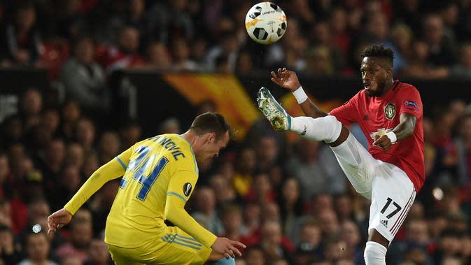 Gelandang Manchester United, Fred, menghindari penjagaan bek Astana, Luka Simunovic, pada laga Europa League di Stadion Old Trafford, Manchester, Kamis (19/9). MU menang 1-0 atas Astana. (AFP/Oli Scarff)