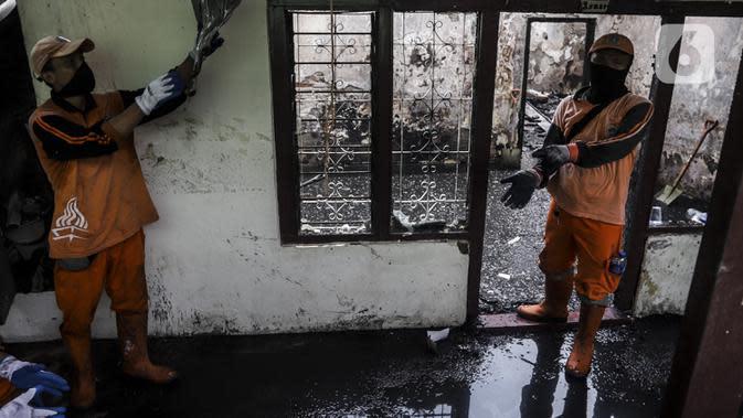 Petugas membersihkan sisa kebakaran di permukiman padat Kelurahan Bali Mester, Jatinegara, Jakarta, Selasa (8/9/2020). Kebakaran di permukiman padat itu melalap 11 rumah tinggal warga serta satu unit bengkel dan mengakibatkan 60 orang mengungsi. (Liputan6.com/Johan Tallo)