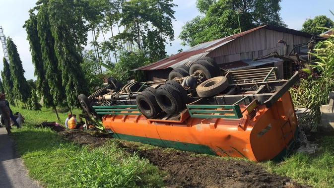 Hingga akhirnya truk terguling keluar dari jalan tol dan jatuh menimpa dinding pembatas rumah warga