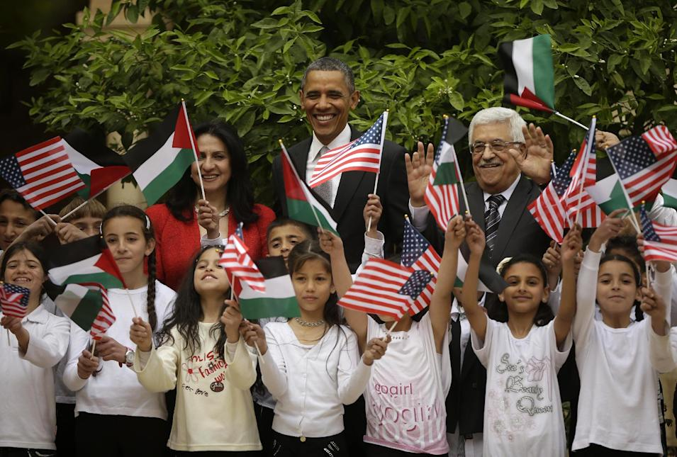 President Barack Obama, flanked by Palestinian President Mahmoud Abbas, right, and Bethlehem Mayor Vera Baboun,  are joined by children at the Church of the Nativity during their visit to the West Bank city of Bethlehem, Friday, March 22, 2013. (AP Photo/Pablo Martinez Monsivais)