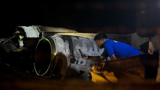 Petugas memeriksa puing-puing pesawat yang mengalami kecelakaan di ujung landasan pacu 24 di Bandara Internasional Ninoy Aquino, Manila, Filipina (29/3/2020). Pesawat Lionair mengalami kecelakaan di Manila pada Minggu malam, 29 Maret 2020. Total delapan penumpang tewas. (Xinhua/Rouelle Umali)