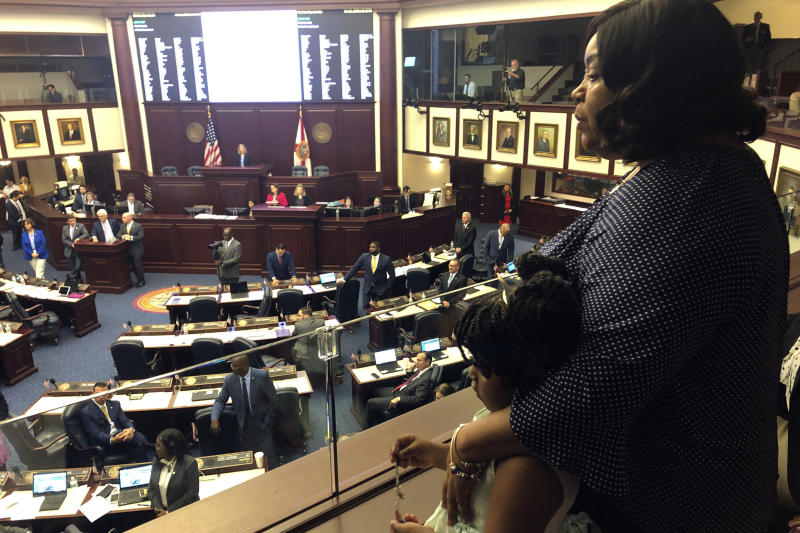 "Meralyn Kirkland holds her granddaughter Kaia Rolle as legislaors work on the House floor, Wednesday, March 4, 2020, in Tallahassee, Fla. Florida lawmakers rallied behind a 6-year-old Rolle who was zip-tied at school and arrested last fall, and on Wednesday inserted an amendment into a school safety bill to require authorities to disclose their policies and procedures for arresting children under 10 years old. The scene generated public outrage when footage from a police body camera showed the crying young girl pleading with the arresting officer for ""a second chance."" (AP Photo/Bobby Caina Calvan)"