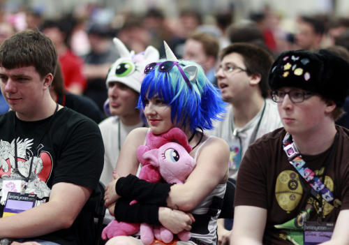 "My Little Pony cartoon fans, some in Little Pony costumes, listen to a presentation at ""BronyCon"" Saturday, June, 30, 2012, in Secaucus, N.J. This weekend's ""BronyCon Summer 2012"" at the Meadowlands Exposition Center attracted 4,000 men, women, boys and girls, many in colorful wigs and costume. (AP Photo/Mel Evans)"