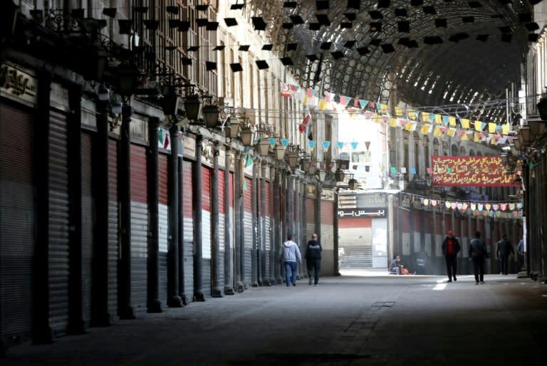 People walk through the shuttered century-old covered bazaar of Hamidiya in Syria's capital Damascus
