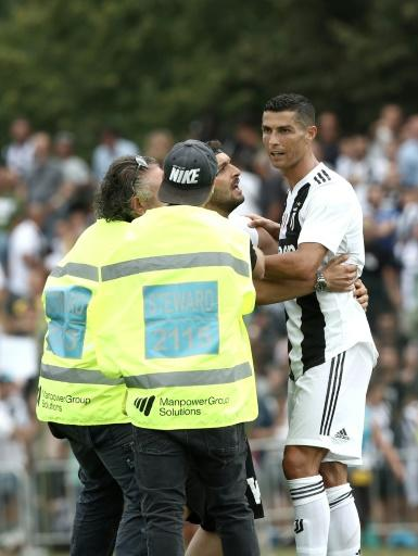 In demand: Juventus supporters invade the pitch to take a picture with Cristiano Ronaldo