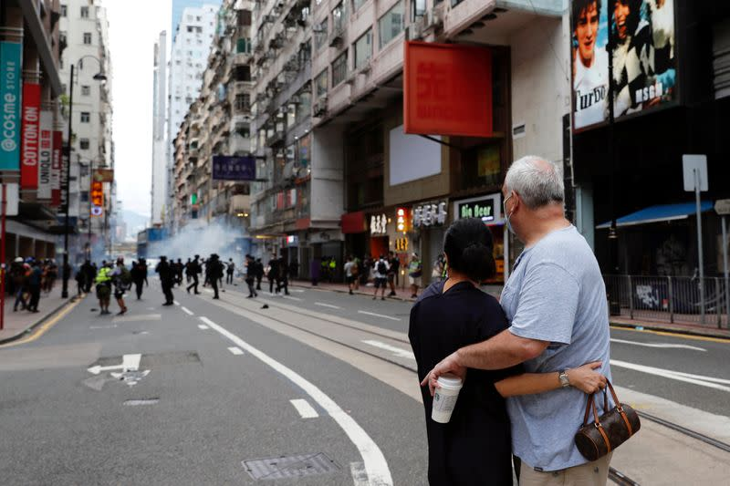 Couple hug each other as police fire tear gas into the crowds to disperse anti-national security law protesters during a march at the anniversary of Hong Kong's handover to China from Britain in Hong Kong