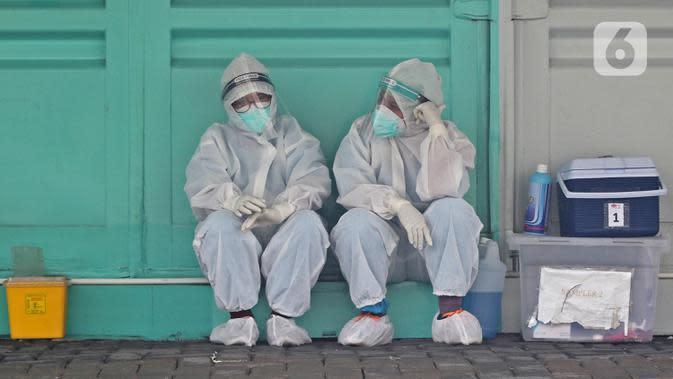 Tenaga kesehatan dengan APD menunggu warga yang akan melakukan tes swab di sekitar GSI Lab (Genomik Solidaritas Indonesia Laboratorium), Jakarta, Sabtu (3/10/2020). Pemerintah telah menyepakati batas maksimal harga tes usap atau swab mandiri sebesar Rp900 ribu. (Liputan6.com/Herman Zakharia)