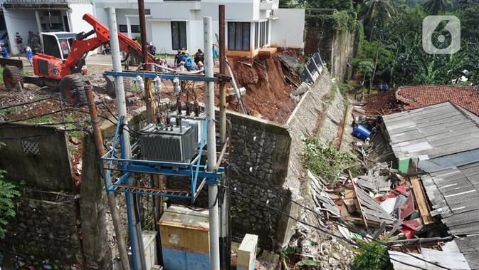 Petugas menggunakan alat berat berusaha merapikan posisi turap yang hancur di Jalan Damai, Ciganjur, Jakarta Selatan, Minggu (11/10/2020). Banjir sekaligus longsor tersebut mengakibatkan dua orang luka-luka dan satu orang meninggal dunia. (Liputan6.com/Immanuel Antonius)