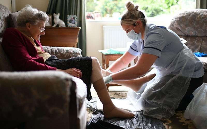 A nurse, wearing personal protective equipment changes the dressings on the legs of an elderly woman - PA