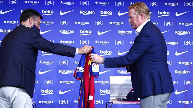 Presiden Barcelona, Josep Maria Bartomeu, memberikan jersey kepada pelatih baru Barcelona, Ronald Koeman, saat acara perkenalan di Barcelona, Rabu (20/8/2020). Koeman resmi menjadi pelatih Barcelona untuk dua tahun kedepan. (AP/Joan Monfort)