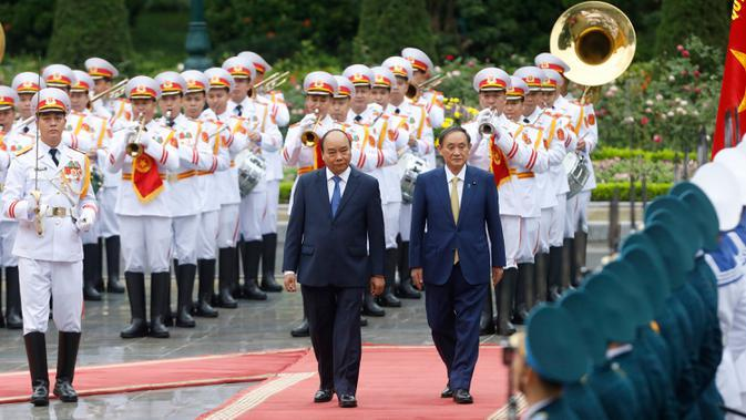 PM Jepang, Yoshihide Suga (kanan) bersama PM Vietnam, Nguyen Xuan Phuc saat upacara penyambutan tamu negara di Istana Kepresidenan, di Hanoi, Vietnam, Senin (19/10/2020). Yoshihide Suga melakukan kunjungan resmi ke Vietnam hingga 20 Oktober 2020. (Kham/Pool Photo via AP)