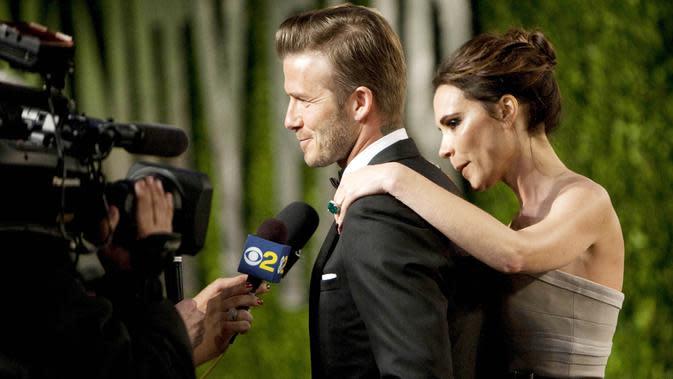 Legenda Timnas Inggris, David Beckham, bersama istrinya, Victoria Beckham, memberikan keterangan kepada wartawan saat menghadiri acara Vanity Fair Oscar Party di Sunset Tower, California, Amerika Serikat (26/2/2012). (Photo by ADRIAN SANCHEZ-GONZALEZ / AFP)