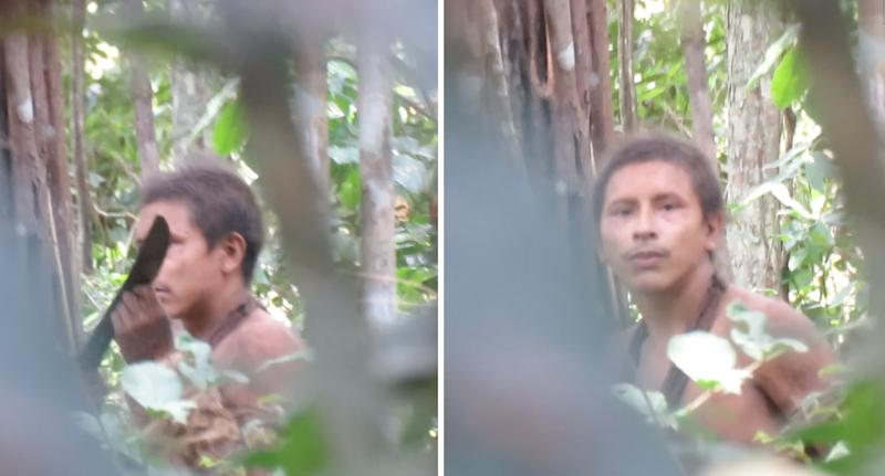 A man can be seen through the forest staring back at the camera.