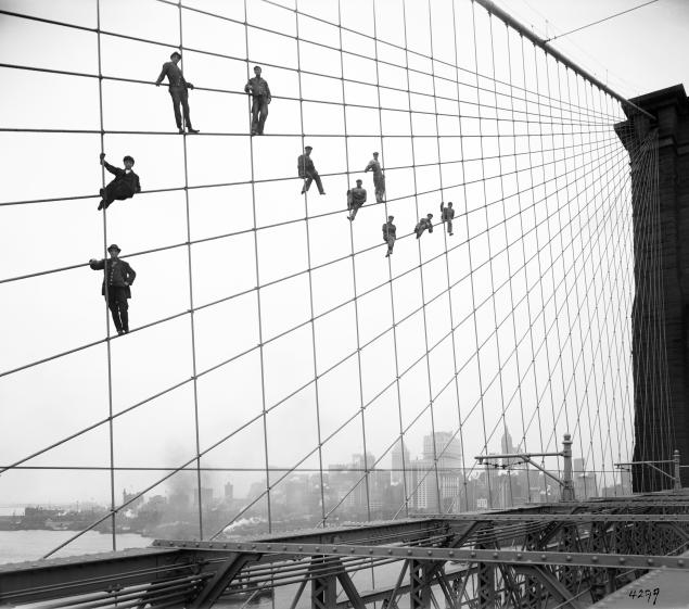 In this Oct. 7, 1914 photo provided by the New York City Municipal Archives, painters are suspended from wires on the Brooklyn Bridge in New York. Over 870,000 photos from an archive that exceeds 2.2 million images have been scanned and made available online, for the first time giving a global audience a view of a rich collection that documents life in New York City. (AP Photo/New York City Municipal Archives, Department of Bridges/Plant & Structures, Eugene de Salignac) MANDATORY CREDIT