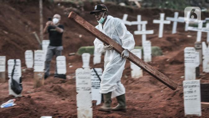 Petugas melintasi area pemakaman protap Covid-19 di TPU Pondok Ranggon, Jakarta, Senin (28/9/2020). Pemprov DKI Jakarta mencatat 1.372 orang dimakamkan dengan protap Covid-19 periode 1-25 September 2020 dan merupakan angka tertinggi selama pandemi sejak Maret lalu. (merdeka.com/Iqbal S. Nugroho)