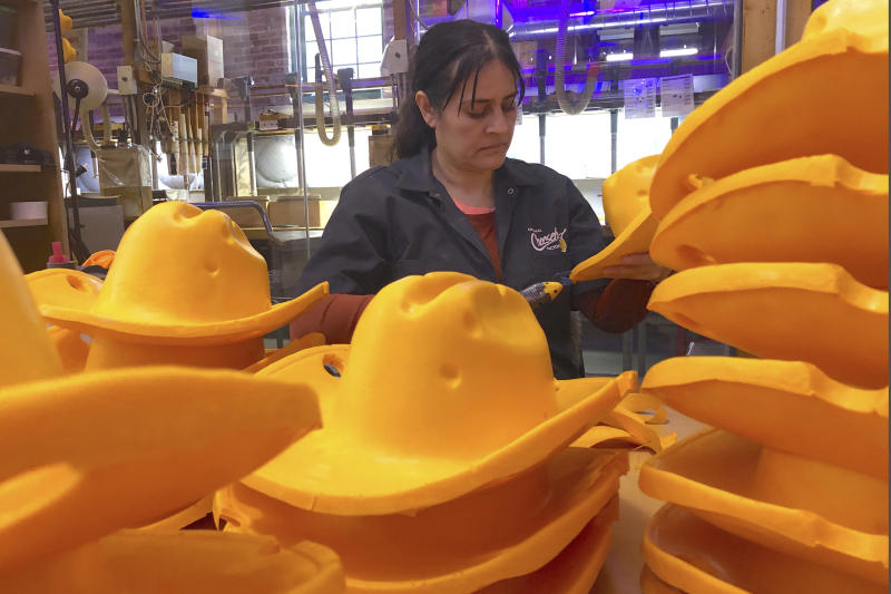 This Jan. 13, 2020 photo shows Maria Hernandez trimming foam cowboy hats at Foamation, Inc. in Milwaukee. Ralph Bruno invented the yellow wedge cheesehead in 1987 from his mother's couch stuffing and it has since become popular, particularly for Wisconsin sports fans and residents.  His company, Foamation, Inc., which makes other foam products like these cowboy hats, moved into a new location in 2016 and soon started tours where people can make their own cheeseheads or other foam products.  (AP Photo/Carrie Antlfinger)