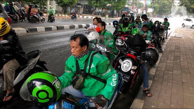 Pengendara sepeda motor berteduh di kolong flyover saat hujan mengguyur kawasan Tebet, Jakarta, Senin (14/9/2020). Kolong flyover kerap menjadi tempat berteduh bagi sebagian pengendara, meski kondisi tersebut dapat mengganggu arus lalu lintas. (Liputan6.com/Immanuel Antonius)
