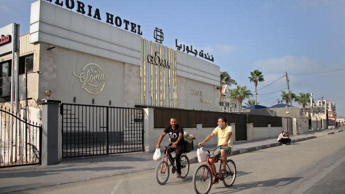 Warga Palestina bersepeda melewati sebuah hotel di Gaza City, 17 September 2020. Lebih dari 500 tempat wisata di Gaza, termasuk hotel, restoran, gedung pernikahan, dan kafe, telah ditutup menyusul penerapan lockdown yang menyebabkan 7.000 pekerja menganggur sementara. (Xinhua/Rizek Abdeljawad)