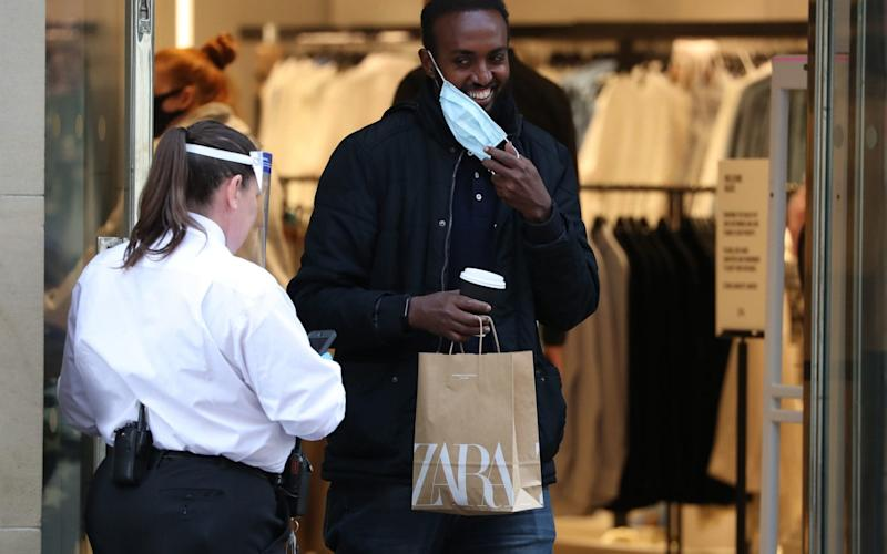 A man removes his face mask as he leaves a store on Buchanan Street in Glasgow as it became compulsory to wear face coverings in shops from today in Scotland - Andrew Milligan / PA