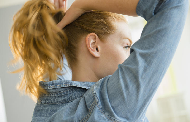 Pictured is a woman tying her hair back into a pony tail with a hair elastic.