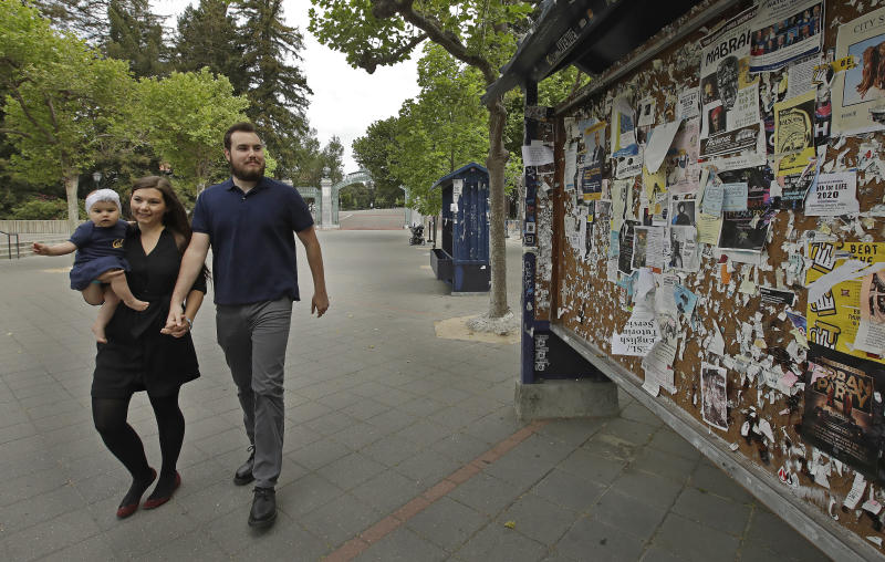 "University of California at Berkeley graduate Tyler Lyson walks with his wife, Lucie, who is holding their 8-month-old daughter, Lisa, as they walk past a student activity billboard on the closed Cal campus in Berkeley, Calif., on Monday, May 11, 2020. The 28-year-old won a full scholarship to the University of California-Berkeley and will become the first in his family to earn a degree. ""I'm supposed to be doing great,"" he said. Instead, he feels powerless and panicked, with a political science degree that seems worthless. (AP Photo/Ben Margot)"
