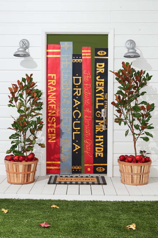 """<p>Before scary movies, there were horror novels. So why not incorporate the classics right onto your Halloween door—especially if you're wearing a <a href=""""https://www.countryliving.com/diy-crafts/g28594281/book-character-costumes/"""">book character costume</a>?</p><p><strong>Make the Book Door</strong><strong>: </strong>Cut long, thin rectangular pieces of differing colored kraft paper (we used red, gray, and black). Draw titles of books on the paper. Outline letters with gold paint pens. Fill in outline with paint pen or gold acrylic paint. Attach to door with double-sided tape. Add large bushel basket and buffalo-check doormat.<strong></strong></p><p><strong></strong><a class=""""body-btn-link"""" href=""""https://www.amazon.com/Rainbow-Kraft-200-ft-Flame-0063064/dp/B0062TMTXE/?tag=syn-yahoo-20&ascsubtag=%5Bartid%7C10050.g.22350299%5Bsrc%7Cyahoo-us"""" target=""""_blank"""">SHOP KRAFT PAPER</a></p>"""