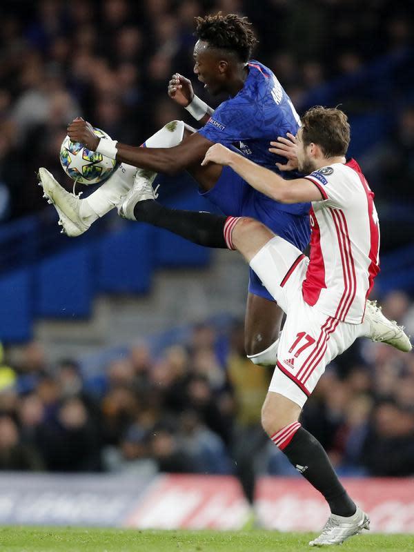 Penyerang Chelsea, Tammy Abraham berebut bola dengan bek Ajax, Daley Blind pada pertandingan lanjutan Grup H Liga Champions di Stamford Bridge, London (5/11/2019). Chelsea bermain imbang 4-4 atas Ajax. (AP Photo/Frank Augstein)
