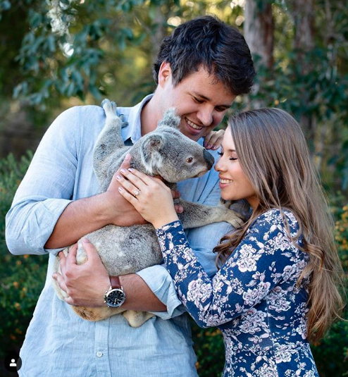 Bindi Irwin and fiancé Chandler Powell pose on their engagement with a koala at Australia Zoo