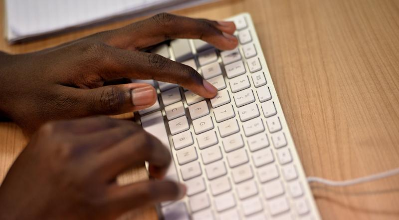 A man types on an Apple keyboard
