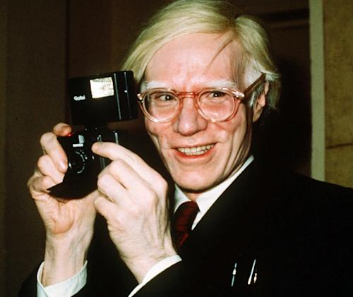 FILE - In this 1976 file photo, pop artist Andy Warhol smiles in New York. The Andy Warhol Museum is launching a live video feed from the pop artist's gravesite to honor his 85th birthday. Warhol's 85th birthday would have been Tuesday, Aug. 6, 2013. Warhol died in 1987. (AP Photo/Richard Drew, File)