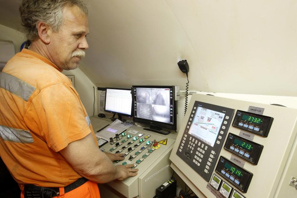 An employee looks on monitors to control the mixture of concrete on the special train 'Helvetia' in the NEAT Gotthard Base tunnel near Erstfeld